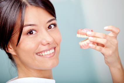 Woman holding dentures